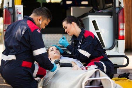 Paramedic team examining pateint