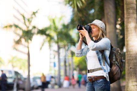 Photo pour Touriste féminine prenant des photos dans la ville urbaine - image libre de droit