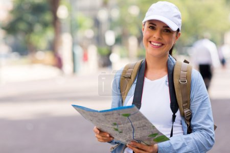 Beautiful young tourist holding a map in urban street