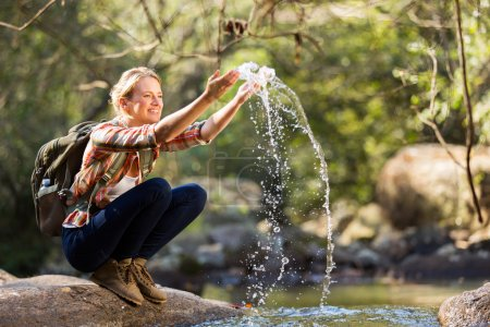 Photo for Young female hiker playing with stream water - Royalty Free Image