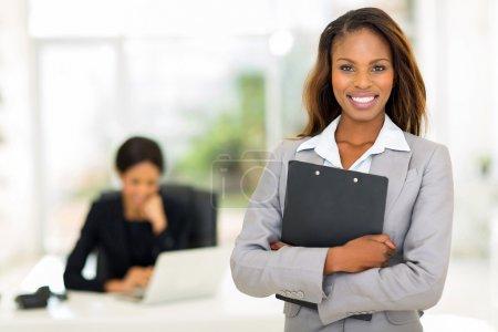 Photo pour Femme d'affaires noirs tenant des presse-papiers avec collègue sur fond - image libre de droit