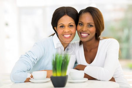 mid age african mother and adult daughter