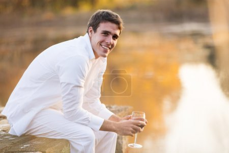 young man holding glass of wine by the pond