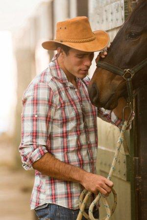 Photo pour Jeune cow-boy qui chuchote dans un cheval dans l'écurie - image libre de droit