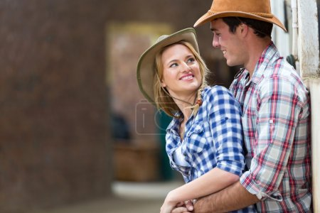 Photo for Happy young farm couple embracing in stables - Royalty Free Image