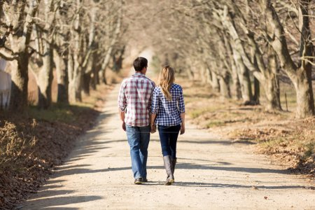 Photo for Rear view of couple holding hands walking in autumn countryside - Royalty Free Image