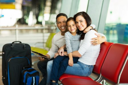 Photo for Loving young family waiting for their flight at airport - Royalty Free Image
