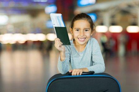 Photo pour Portrait de fillette souriante tenant le passeport et le passent à l'aéroport - image libre de droit