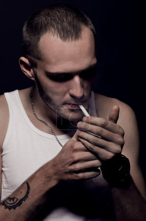 Young man lights a cigarette