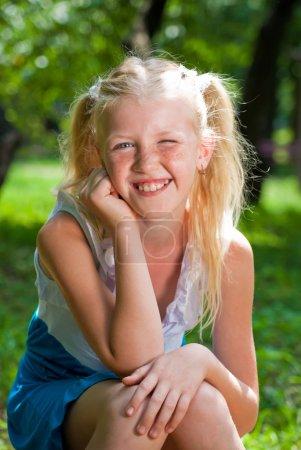 Photo pour Fille blonde douce, joueuse assis dans le jardin verdoyant et la sauvegarde de menton dans sa main - sourires et clins de œil. à première vue un grand nombre de taches de rousseur - image libre de droit