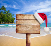 Christmas on beach. Wooden signboard with Santa's hat.