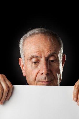 Photo pour Vieil homme avec un papier blanc sur fond noir - image libre de droit