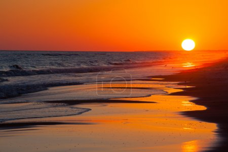 Photo for Sun setting on the beach with orange and yellow sky - Royalty Free Image