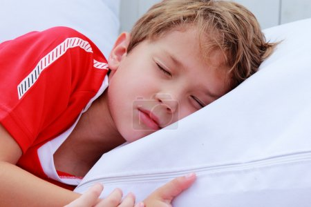 cute 7 years boy sleeping on white pillow in summer cafe