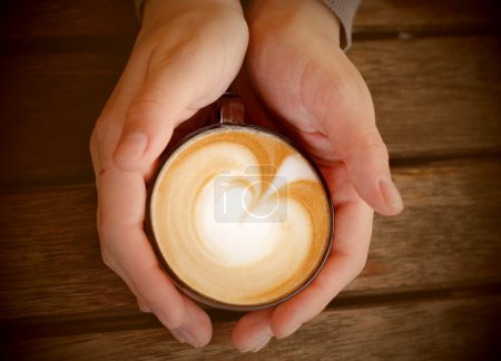 woman hands with cappuccino on a wood table