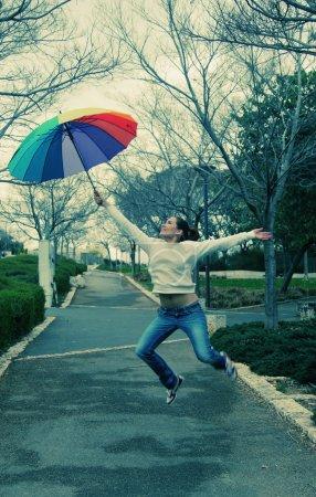 Woman jumpimg with umbrella