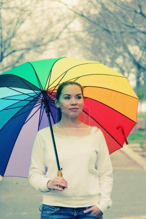 Photo pour Jeune femme sous grand parapluie arc-en-ciel coloré - image libre de droit