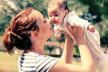 Foto de Retrato de feliz madre cariñosa y su bebé al aire libre - Imagen libre de derechos