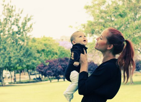 Photo for Portrait of happy loving mother and her baby outdoors - Royalty Free Image
