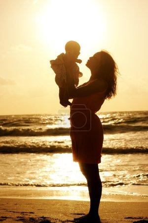 Photo pour Silhouette de la mère et du bébé au coucher du soleil - image libre de droit