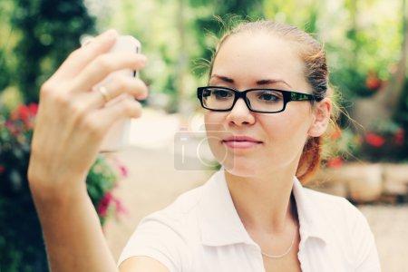 Photo pour Portrait de jeune femme, prendre des photos avec un smartphone en plein air - image libre de droit