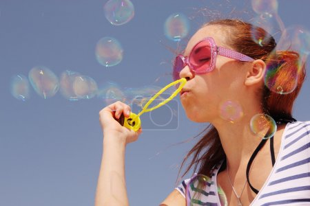 Photo for Pretty girl blowing bubbles in sunny day - Royalty Free Image