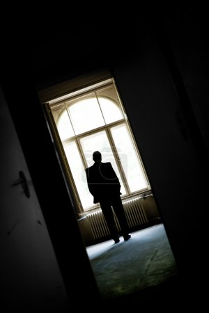 Photo for Man looks out of the empty house window - Royalty Free Image