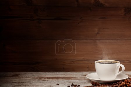 White cup of coffee over wooden background