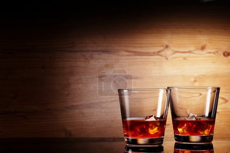 Photo pour Tho verres de whisky sur woodenbackground - image libre de droit