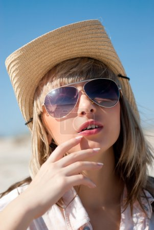 Photo for Portrait of blond woman in cowboy hat and sunglasses on a sandy beach - Royalty Free Image