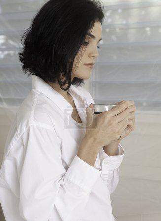 woman by bright window with coffee.