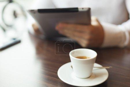 Photo pour Homme avec tablette nouvelles de lecture d'ordinateur à motning dans un café-boutique - image libre de droit