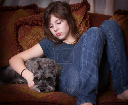 Photo for Cute teenage girl sad and alone on couch with pet dog - Royalty Free Image