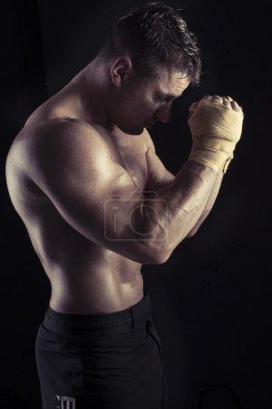 Moody dark portrait of sexy bodybuilder