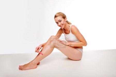 Sexy woman waxing her legs