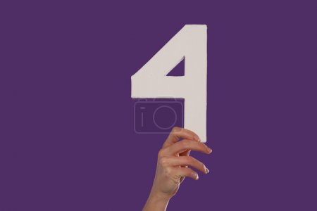 Female hand holding up the number 4 against a purp...