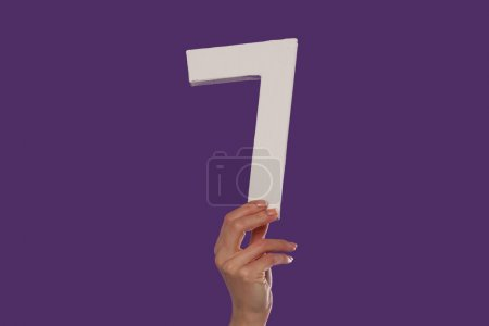 Female hand holding up the number 7 from the bottom
