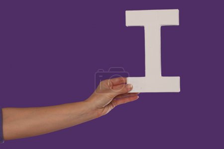 Female hand holding up the letter I from the left