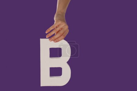 Photo for Female hand holding up the uppercase capital letter B isolated against a purple background conceptual of the alphabet, writing, literature and typeface - Royalty Free Image