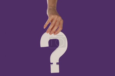 Female hand holding up a question mark from the top