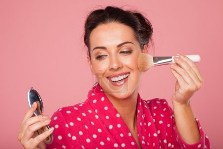 Laughing woman applying blusher