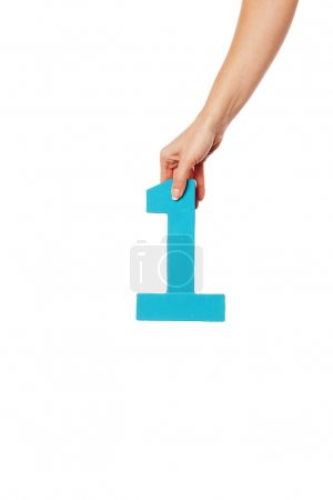 Photo for Female hand holding up the number 1 against a white background conceptual of numbers, measurement, amount, quantity, accounting and mathematics - Royalty Free Image