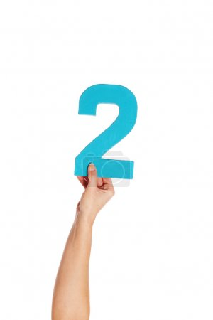 Photo for Female hand holding up the number 2 against a white background conceptual of numbers, measurement, amount, quantity, accounting and mathematics - Royalty Free Image