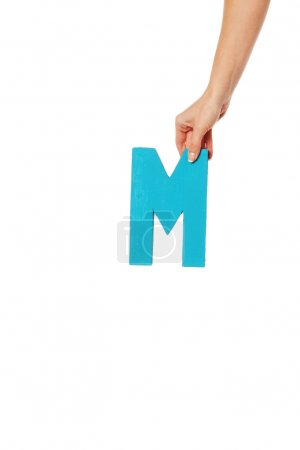 hand holding up the letter M from the top