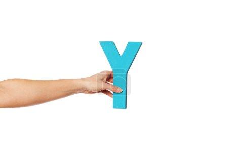 Photo pour Main féminine tenant la majuscule majuscule Y isolée sur un fond blanc conceptuel de l'alphabet, de l'écriture, de la littérature et de la police de caractères - image libre de droit