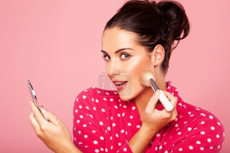 Beautiful young brunette woman applying blusher to...