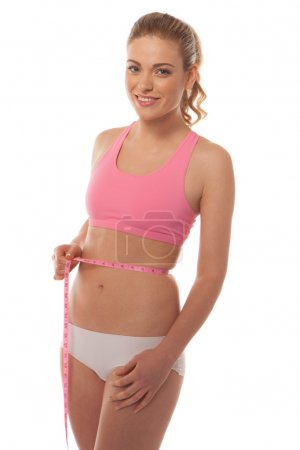 Fit young woman measuring her waist