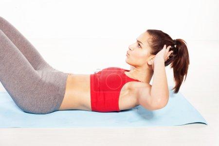 Photo pour Fit jeune femme pratiquant des exercices abdominaux sur le sol - image libre de droit