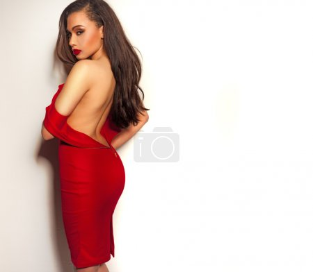 Photo for Beautiful sexy sultry young woman in an off the shoulder red dress standing displaying her bare back to the camera while looking back over her shoulder with a seductive look - Royalty Free Image