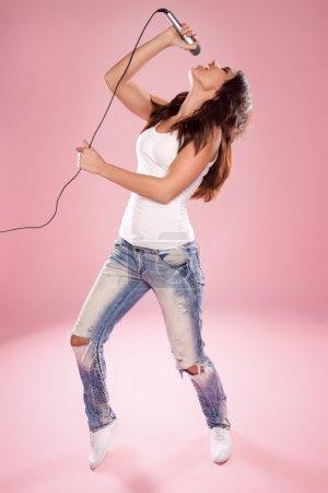 Photo pour Sexy chanteuse tenant un micro portant jeans et haut blanc - image libre de droit